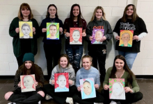 Nine girls, each holding a portrait