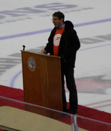 Picture of Jonathan Mueller speaking behind the podium on the Arena rink