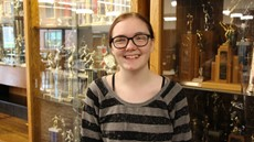 Photo of Autumn Knight in front of High School trophy case