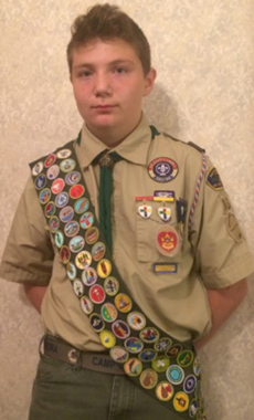 Christian Arsenault in his Boy Scout uniform with a sash of badges