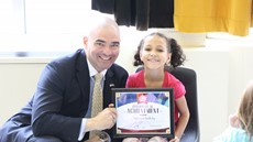 Senator Akshar smiling with Mylee Siedlecki who is sitting, holding her certificate