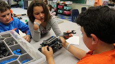 Young girl looking at a robotics part held by a young boy in a classroom
