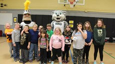Children in school gym posing with Baxter the Bearcat and Black Knight mascots
