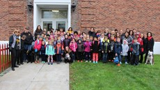 Group photo of dozens of elementary school students with parents and staff on the lawn in front of a brick building
