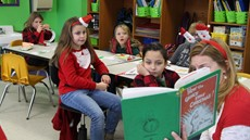 A female teacher wearing Santa ears holds a up a copy of The Grinch Who Stole Christmas while young students look on