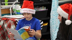 2nd-grade boy in a Santa hat holding a book while a high school female student sits next to him