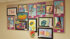 Children's art work hanging on a wall