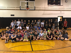 Group photo of dozens of children in t-shirts and shorts sitting on the high school gym floor with a row of bigger children standing behind them