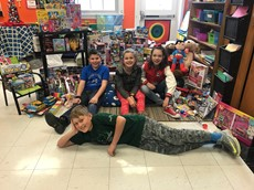Elementary students pose with bags of toys in a classroom
