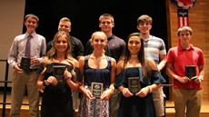 Student-athletes holding their awards