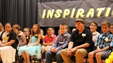 """Children sitting on stage in front of a banner saying """"inspiration"""""""