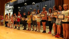 Students on stage holding awards