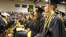 Graduating students sitting in audience in gym in their caps and gowns