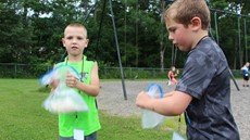 Two young boys shaking plastic bags