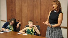 Two children listening to speaker in conference room