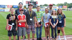 Students with Rumble Ponies players in front of the outfield