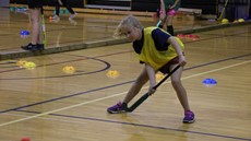 Girl playing field hockey in a gymnasium