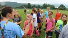 Coach talking to young field hockey players on outdoor field