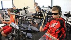 Five children drumming on drum sets