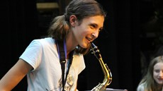 Girl smiling holding a saxophone