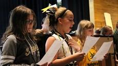 Three girls singing in a chorus