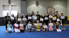 Group picture of cheer camp students, volunteers and coaches on gym mat