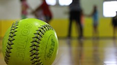 Softball in focus in foreground with children out of focus in background