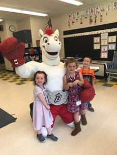 Picture of Rowdy the Pony mascot with three young children