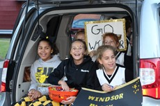 Three smiling young girls in Windsor clothing sitting in open hatch of SUV