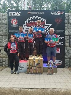 Four people in BMX racing gear on a podium