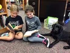 Two young girls sitting on a rug holding books, next to a black lab puppy