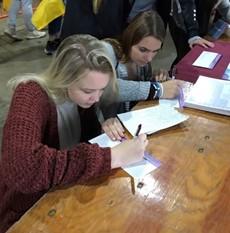 A teenage girl sitting at a desk writing