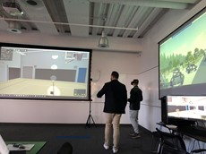 Two people standing in a room with a large screen on each of two walls around them