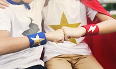 One child with his arm around another giving each other a fist bump