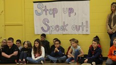 "Children sitting underneath a sign reading, ""Step up, speak out"""