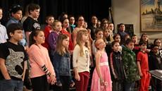 dozens of children singing in a chorus