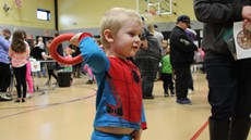 Young boy in a Spider Man suit holding a ring