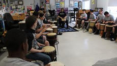 Students sitting in a classroom holding drums