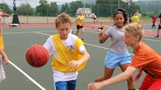 Two boys and a girl playing basketball outside