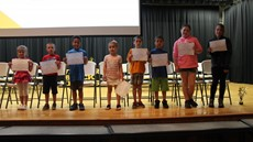 Children standing on stage holding certificates
