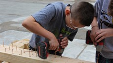 A child drilling screws into a board