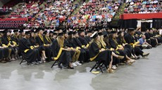 Rows of people in caps and gowns seated on the floor of an arena with people in seats around them