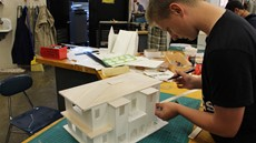 Male student working on a model of a house