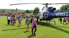 A line of children walking around a helicopter in a field
