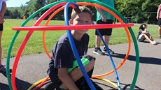 A boy sitting in a structure made of colorful hula hoops