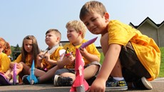 A handful of small children sitting on blacktop with cardboard rockets