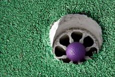 Purple golf ball in a hole