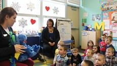 A woman sitting in front of a classroom of pre-k student