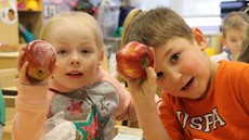 Two young children holding apples