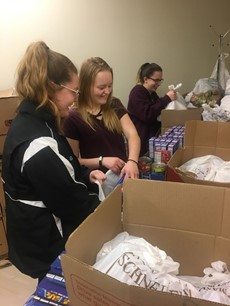 3 high school girls packing food into boxes
